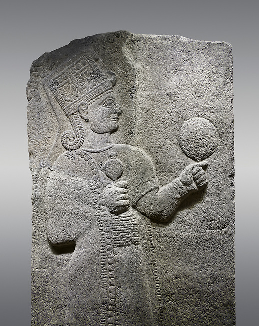 Picture & image of Hittite relief sculpted orthostat stone panel of Long Wall Basalt, Karkamıs, (Kargamıs), Carchemish (Karkemish), 900 - 700 B.C. Anatolian Civilizations Museum, Ankara, Turkey.<br /> <br /> Goddess Kubaba. Goddess is depicted from the profile. The part below the chest of the relief is broken. She holds a pomegranate in her hands on her chest. She carries a one-horned headdress on her head. Her braided hair hangs down to her shoulder. The text in the hieroglyphics is not understood. The lower part of the relief has been restored. <br /> <br /> On a gray background.