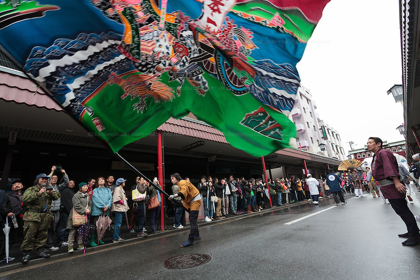 A festival supports waves a large flag during the Kanamara festival for the steel phallus in Kawasaki Daishi, Kanagawa, Japan. Sunday April 5th 2015 The Kanamara penis festival celebrates a legend about the defeat of a penis-eating demon. It is a wildly popular festival attracting large numbers of locals and foreigners.