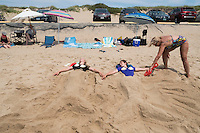 Sisters Chloe, 15, and Amelie, 16, Lachance-Soulard (from left), of Ottawa, Canada, lay buried under sand sculptures of mermaid tails at Herring Cove Beach in the Cape Cod National Seashore outside of Provincetown, Mass., USA, on Fri., July 1, 2016. Portions of the parking lot have been closed after land eroded during storms earlier this year. This was the girls' first visit to the area.