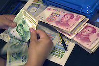 A woman counts Renminbi (RMB) in Beijing, China..