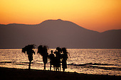 Mahale, Tanzania. Group of people walking beside Lake Tanganyika carrying fodder on their heads at sunset.