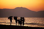 Mahale, Tanzania. Group of people walking beside Lake Tanganyika carrying fodder on their heads at sunset.