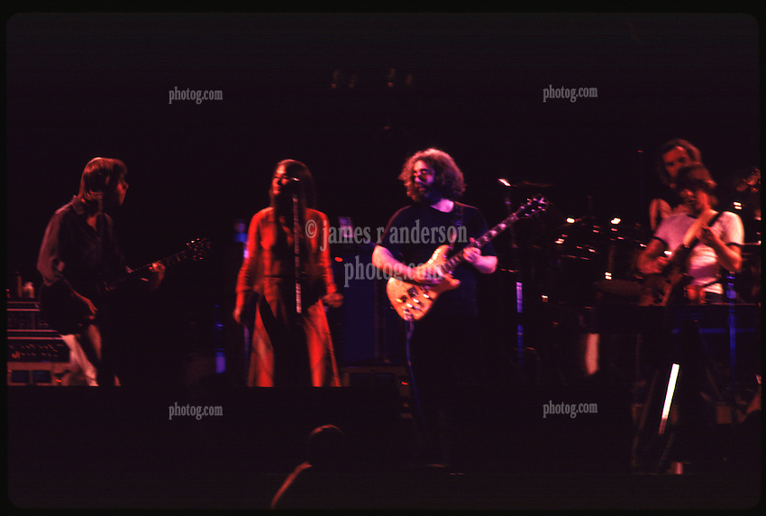 Grateful Dead in Concert at the Huntington Civic Center, Huntington West Virginia on 16 April 1978. Most of the Band in this image. Bob Weir, Donna Godchaux, Jerry Garcia, Bill Kreutzmann and Phil Lesh. Missing out of frame: Mickey Hard and Keith Godchaux. Image No. 78C15-26