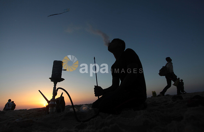 A Palestinian man smokes hookah on a beach in Gaza City May 2, 2014. Photo by Ashraf Amra