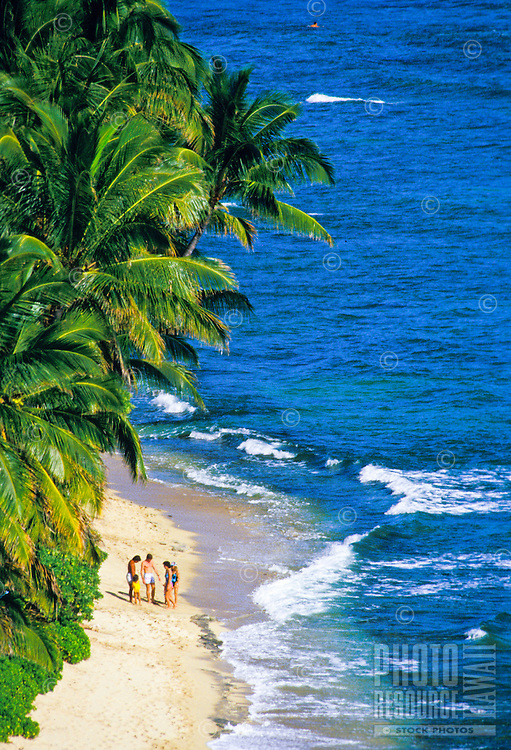 Family strolling along a secluded stretch of Diamond Head Beach, Oahu.