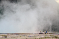 TOURISTS AND A PHOTOGRAPHER ARE DWARFED BY THE HIGH PLUMES OF STEAM PRODUCED AT THE MIDWAY GEYSER BASIN AT YELLOWSTONE NATIONAL PARK,WYOMING