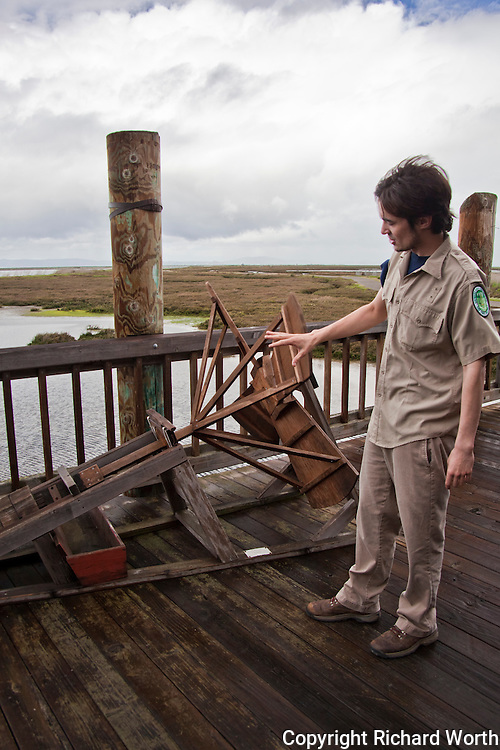 A small replica of an Archimedes Screw Pump that once aided in the salt harvesting along the San Francisco Bay is demonstrated by Naturalist Christopher Cook of the Hayward Area  Recreaton and Park  District.  Hayward Shoreline Interpretive Center, Hayward, California.