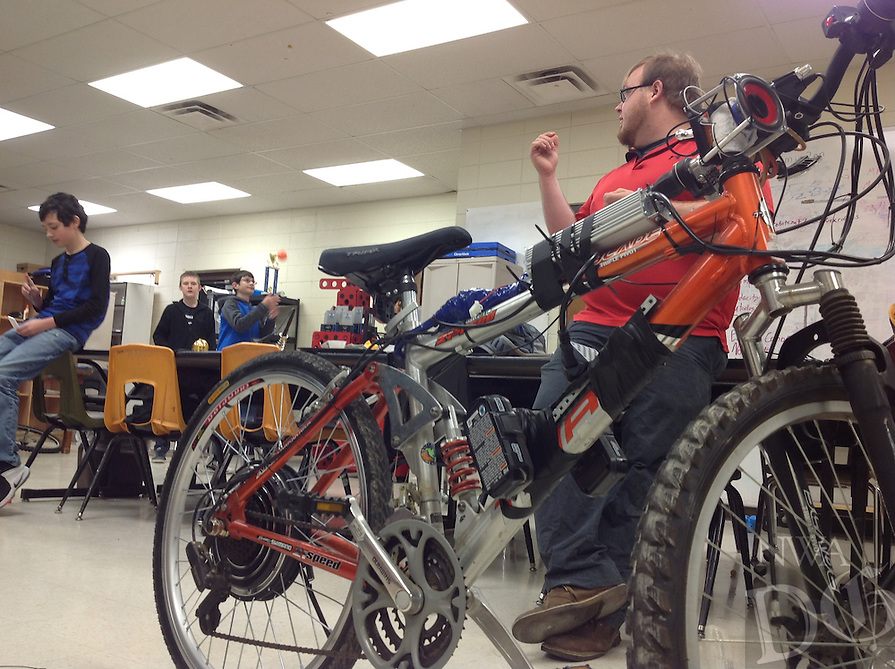 NWA Democrat-Gazette/Dave Perozek<br /> Blake Matthews (right), a science and technology teacher at Washington Junior High School, chats in his classroom Tuesday (Jan. 31) about the electric bicycle his students assembled last month.