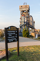 A sign indicates mileage to landmarks on the Arkansas River Trail in Little Rock, Arkansas.