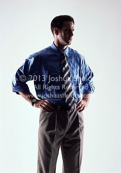 Caucasian looking man wearing a blue shirt and tie looking sideways