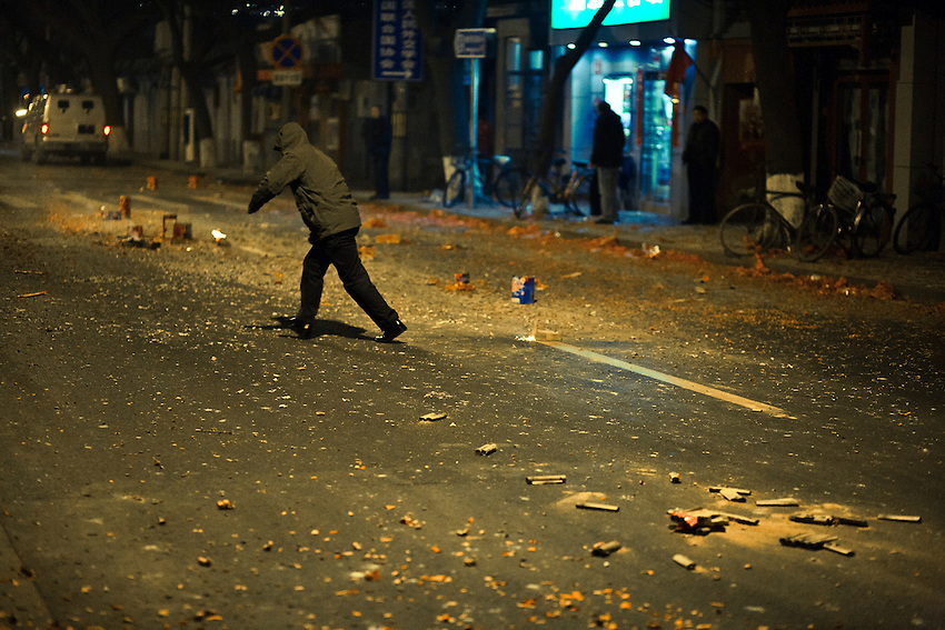 A man is running to cover after he has lighted firecrackers in a street of Beijing, near the forbidden city to celebrate the Chinese new year 2011 , thursday february 3.