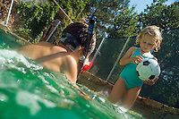 Little girl playing with a soccer ball while her brother snorkels in a swimming pool, Provence, France.