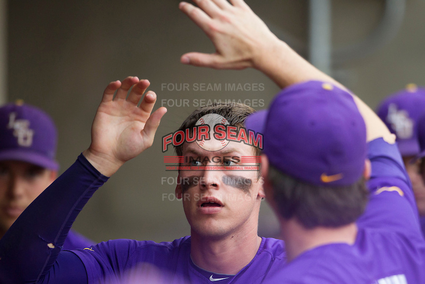 LSU Tigers second baseman Jacoby Jones (23) is greeted in the dugout after scoring against the Texas A&M Aggies in the NCAA Southeastern Conference baseball game on May 10, 2013 at Blue Bell Park in College Station, Texas. LSU defeated Texas A&M 7-4. (Andrew Woolley/Four Seam Images).