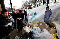 ROMANIA / Bucharest / 21.02.09..Boxes of bread lie amidst makeshift plastic tents across from the Chinese Embassy...Hundreds of Chinese immigrants are currently stuck in Romania after their work contracts with construction firms here were suddenly terminated in late January. They expected to make at least 800 Euros per month, or double what they can make in China as agricultural laborers. About 80 of them are camped out under plastic sheeting in front of the Chinese Embassy hoping to get some kind of help. During the day, hundreds more are joining them to stage a protest. They paid a Chinese broker 10,000 Euros a piece for the lucrative four year construction contracts and are hoping to get reimbursed in order to be able to buy tickets home. The immigrants are relying upon the help of generous Romanians who pull up and deliver food from their cars. The economic crisis hit Romania just as many of the immigrants arrived in November. ...© Davin Ellicson / Anzenberger