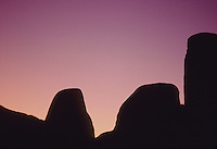 Stock photo of desert boulders and cliffs outlined in silhouette by a purple sunset sky.