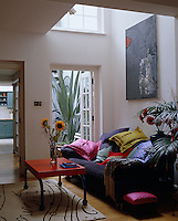 Scattered Cambodian silk cushions and a footstool covered in bright pink silk brighten up this contemporary living room