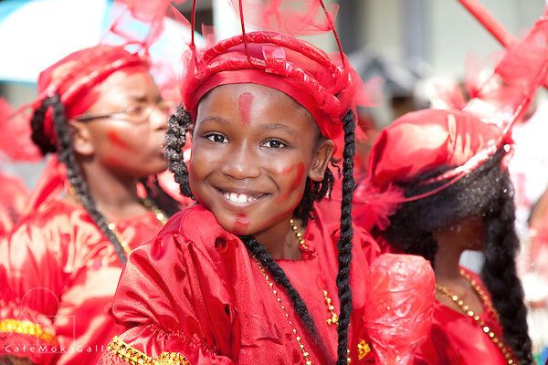 Trinidad Carnival, Junior Traditional Mas parade, winning smile of a girl playing Black Indians in red costumes