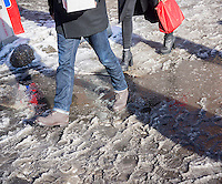Pedestrians slog through puddles of slush and snow at street crossings with snow dam clogged storm drains in the Lower East Side neighborhood of New York on Sunday, February 22, 2015.  (© Richard B. Levine)
