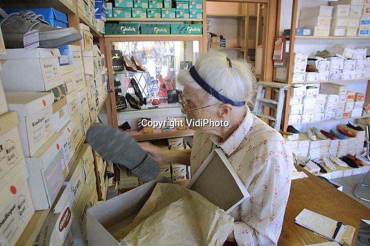 """Foto: VidiPhoto..DRIEL - De oudste schoenmaakster van Nederland, de bijna 92-jarige Marietje van Hagen uit het Betuwse Driel, gaat met pensioen. Ze begon op twaalfjarige leeftijd bij haar vader in de winkel. Na tachtig jaar hard werken doet ze de winkel over drie weken definitief op slot. Met pijn in het hart, dat wel. """"Want ik ga dit zeker missen""""."""