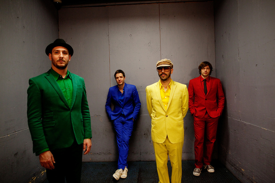 """Los Angeles, California, November 27, 2010 - A portrait of the band Ok Go, from left .drummer, Dan Konopka (green), lead singer/guitarist, Damian Kulash (blue), bass guitarist/singer, Tim Nordwind (yellow), and guitarist/singer, Andy Ross (red),.in a freight elevator at the Nokia Club. OK Go was wrapping up a 16-month world tour by playing a song for Yo Gabba Gabba! during the day and later a final show at the Nokia Club. The Grammy Award-winning band has earned considerable fame for their creative, often low-budget music videos that are released on YouTube. Many have gone viral, including the 2006 video for """"Here It Goes Again"""", where the band performs a complex routine on treadmills. It has received over 50 million views to date. Kulash says the band left their major label and began their own to assert more creative control over their music and their videos. Adding, """"We're among the first musicians to view our YouTube videos as standalone artistic output, not advertisement for our recordings, and it shows in the numbers: over the past decade, we've sold a little over 600,000 records globally, and our videos have combined views in excess of 125 million.""""."""