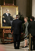 United States President George W. Bush, First Lady Laura Bush and Supreme Court Judge Antonin Scalia pause in front of a portrait of Chief Justice William Rehnquist Sept. 6, 2005 in the Great Hall of the Supreme Court in Washington, DC. Rehnquist's casket will lie in repose at the court until the next morning and he will be buried in a private ceremony at Arlington Cemetery that afternoon.<br /> Credit: Chip Somodevilla / Pool via CNP