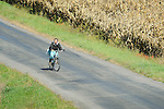 Mennonite woman on bicycle on country road.