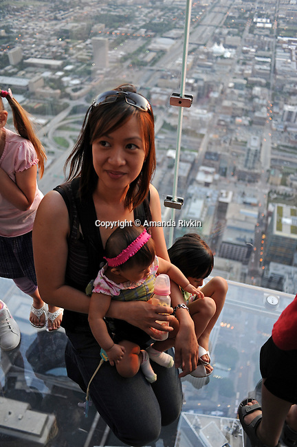 "A visitor sits with her children on the newly opened glass balconies ""The Ledge"" at the Skydeck at the Sears Tower in Chicago, Illinois on July 6, 2009."