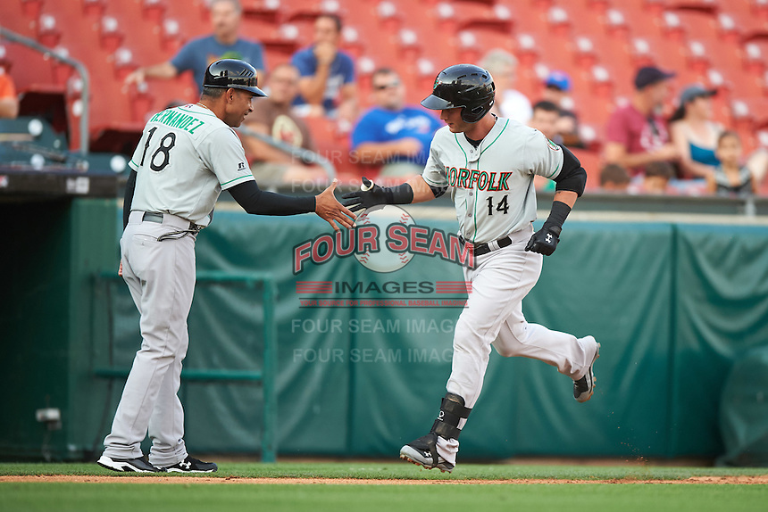 Norfolk Tides coach Jose Hernandez (18) shakes hands with designated hitter Christian Walker (14) after a home run during a game against the Buffalo Bisons on July 18, 2016 at Coca-Cola Field in Buffalo, New York.  Norfolk defeated Buffalo 11-8.  (Mike Janes/Four Seam Images)