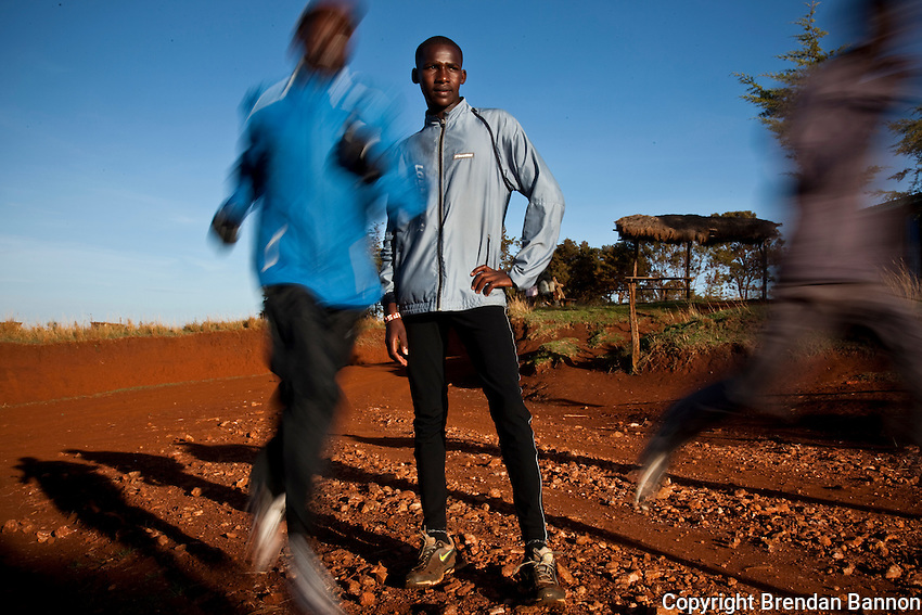 Johanna Kariankei, 17, stands (gray jacket) as his training colleagues speed past him during an early morning run close to the Kenyan town of Iten. Athletes there are being hit by the economic crisis which is robbing races and runners of crucial sponsorship. Johanna, who has never run outside Kenya, hopes the crisis will pass and he will be able to fulfil his dream of winning good money from international races.