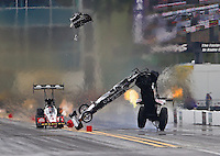 Mar 14, 2015; Gainesville, FL, USA; NHRA top fuel dragster driver Larry Dixon (right) crashes alongside Doug Kalitta after his car broke in half during qualifying for the Gatornationals at Auto Plus Raceway at Gainesville. Dixon walked away from the incident. Mandatory Credit: Mark J. Rebilas-