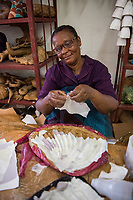 Haiti, Port-au-Prince, Caribbean Craft, artisans factory making products mostly in paper mache and metal work for export. Produce products for outlets such as Toms, and West Elm. Woman that was happy to get a job as her husband beat her so badly he knocked her teeth out and she was able to buy herself a new pair of teeth.