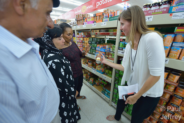 Penny Gushiken (right) leads a cultural orientation class for newly arrived refugees in Lancaster, Pennsylvania. During a visit to a supermarket, participants discuss available food items, including canned goods. The class is sponsored by Church World Service. <br /> <br /> Photo by Paul Jeffrey for Church World Service.