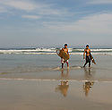 Two ocal surfers after a surfing session at Guaruja's main Beach in Brazil.
