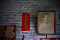 A hundred-year-old portrait of a woman who left to live and work in southeast Asia is hanging at an old house in the ancient Huangxi village of Dali in Foshan city, Guangdong province, November 11, 2011.