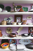 A variety of dishes, pots and collectibles is displayed on open shelves in the kitchen