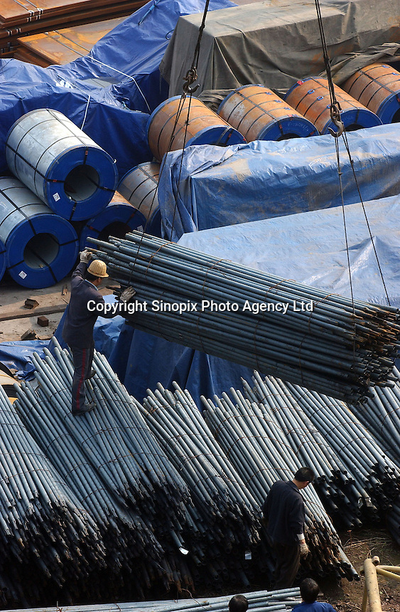 "Steel poles and sheet steel are unloaded at a port in Chongqing. Chongqing is China's largest city and is often termed a ""super-city"". It is at the far shore of the 600 km long Three Gorges Dam and is the ""gateway to western China"". Large sums of money are being pumped into the area and infrastructural projects and building development is ongoing..20-NOV-04"