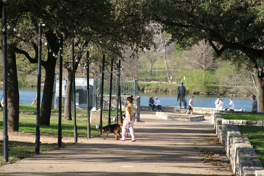 Dog walkers and tourist enjoy the SRV Stevie Ray Vaughn Memorial Statue at Auditorium Shores on Town Lake.