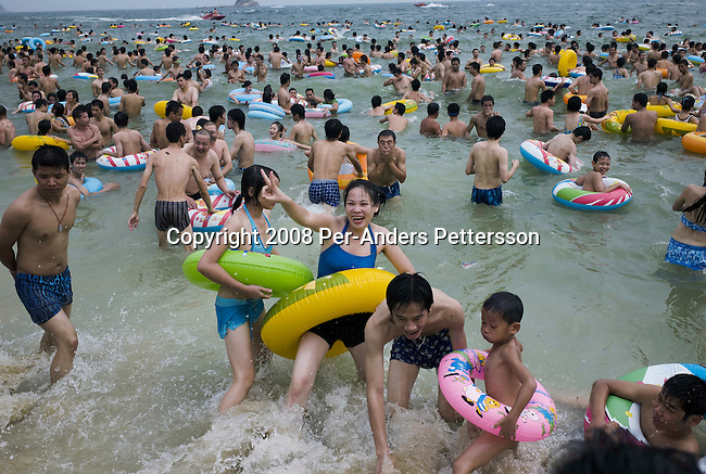 SHENZHEN, CHINA OCTOBER 2: Chinese holidaymakers play in the sea at Dameisha Beach Park on October 2, 2008 outside Shenzhen, China. Millions of Chinese took a weeklong break during the National Holiday and one of the Golden weeks during the year. This is the most popular beach outside Shenzhen, and it's free. The park also has carnival rides and a statue park. Chinese people love theme parks and new ones are opening constantly. It's estimated that there's about 2400 theme parks in the country. Many of the most popular parks are located around Shenzhen and over the border in Hong Kong. (Photo by Per-Anders Pettersson)....