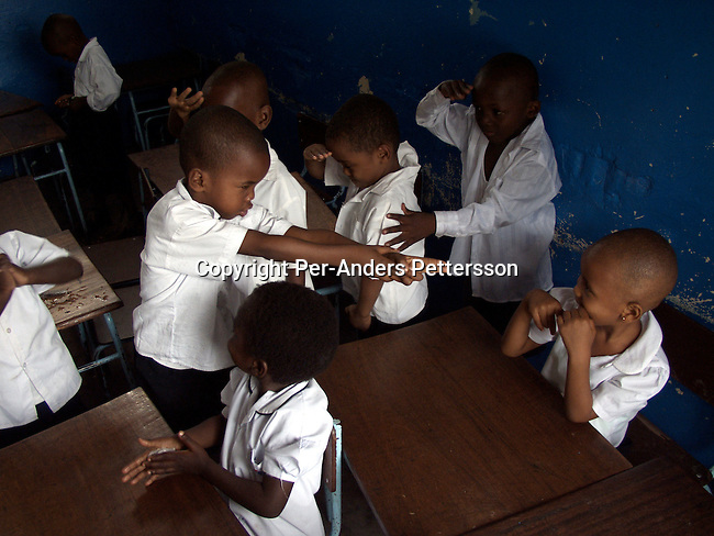 KINSHASA, CONGO - FEBRUARY 28: Unidentified boys acting as soldiers during the singing of patriotic military song in their class on February 28, 2002 at ÒBambiniereÓ a school in Lingwala district, in Kinshasa, Congo. The teacher tells them about the occupation of Rwandan and Ugandan troops in the country..Photo: Per-Anders Pettersson/ Getty Images.....