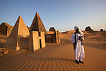 Nubian guide in front of an ancient pyramid (Mut temple?) on the Meroe Site.<br />