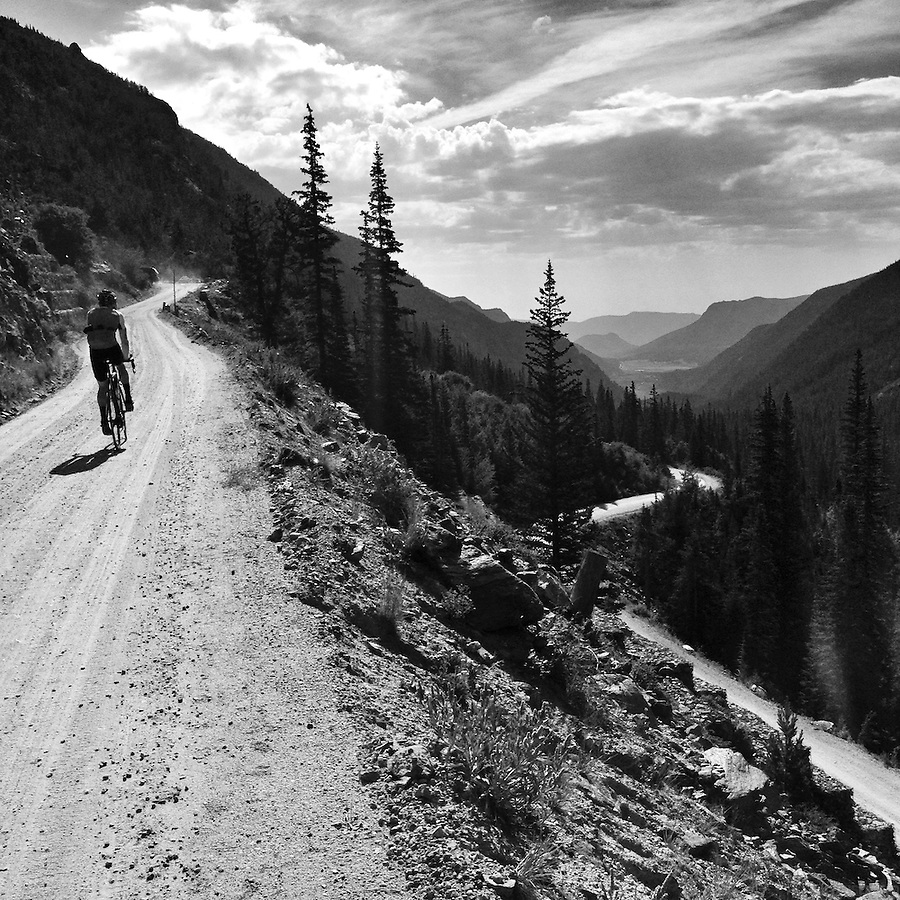 A lone cyclist ascends Old Fall River Road, the old dirt road that cuts through Rocky Mountain National Park, and climbs to the Continental Divide. It was the first automobile road to penetrate the interior of the park. The road linked the east side of the park near Estes Park with Grand Lake on the west side. Work began in 1913 and was completed between 1918 and 1920. The narrow road was partly replaced by Trail Ridge Road in 1932, which incorporated sections of the Fall River Road.