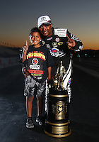 Nov 13, 2016; Pomona, CA, USA; NHRA top fuel driver Antron Brown (right) and son Adler Brown pose for a portrait with the world championship trophy following the Auto Club Finals at Auto Club Raceway at Pomona. Mandatory Credit: Mark J. Rebilas-USA TODAY Sports