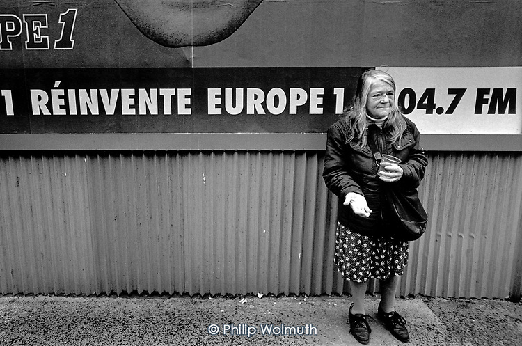 Reinvent Europe. An elderly woman begs in central Paris, France, in front of an advertising hoarding.