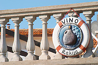 Sign looking like a life buoy advertising Vino wine and Rakija grappa type spirit with a jug of wine and grapes, hanging from a balustrade. Prizba village. Korcula Island. Prizba, Riva Apartments, Danny Franulovic. Korcula Island. Dalmatian Coast, Croatia, Europe.