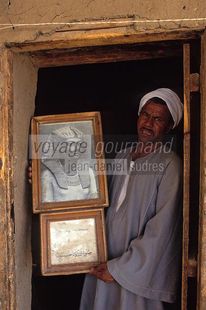Afrique/Egypte/Louxor/Ancienne Thèbes: Temple d'Hatchepoust à Deir El Bahari - Le gardien du temple montre un photographie de la reine Hatchepoust