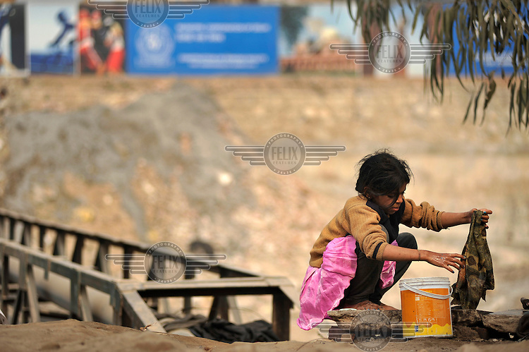 A girl washes clothes in a slum in the area of Nizamuddin East.