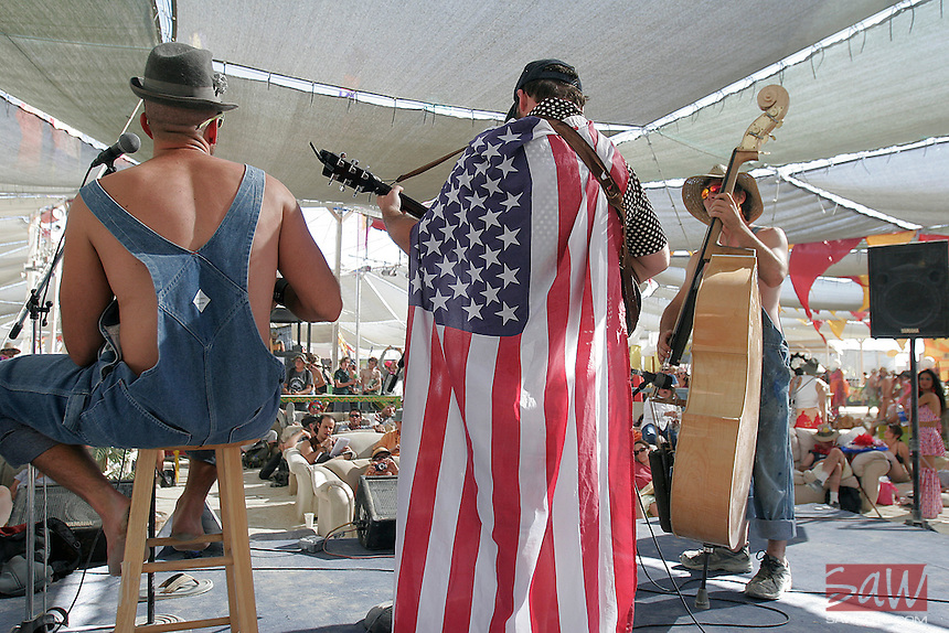 "BLACK ROCK CITY, NV - AUGUST 27,2008:  The theme for Burning Man in 2008 is "" The American Dream"", dressed appropriately, for their performance at center camp, bluegrass group; Jacob Groupman and the little bitches perform, August 27,2008. Participants from around the world are converging in Nevada for the annual art event which attracts over 30,000 people annually."