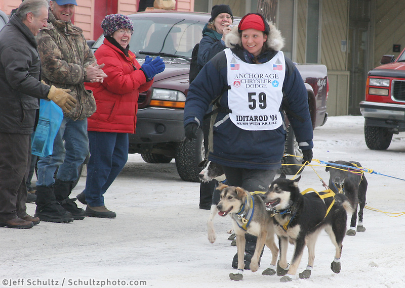 Melissa Owens, the youngest woman to finish the Iditarod, leads her team the final few feet to the finish line in her home town of Nome. Photo by Jon Little.