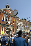Man dressed in Dickensian costume and visitors next to the Old Corn Exchange celebrating the Rochester Dickens Festival