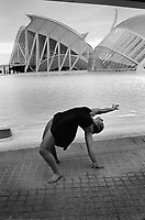 Spain. Valencia Province. Valencia. A young woman dances in front of the futurist building, L'Hemisfèric, at the City of Arts and Sciences, an entertainment-based cultural and architectural complex in the city of Valencia. It is the most important modern tourist destination in the city. The City of Arts and Sciences is situated at the end of the former riverbed of the river Turia, which was drained and rerouted after a catastrophic flood in 1957. The old riverbed was turned into a picturesque sunken park. Designed by Santiago Calatrava and Félix Candela, the project began the first stages of construction in July 1996, and was inaugurated April 16, 1998 with the opening of L'Hemisfèric. Originally budgeted at €300 million, it has cost nearly three times the initial expected cost.Valencia (officially València) is the capital of the autonomous community of Valencia and the third-largest city in Spain. 16.12.18  © 2018 Didier Ruef